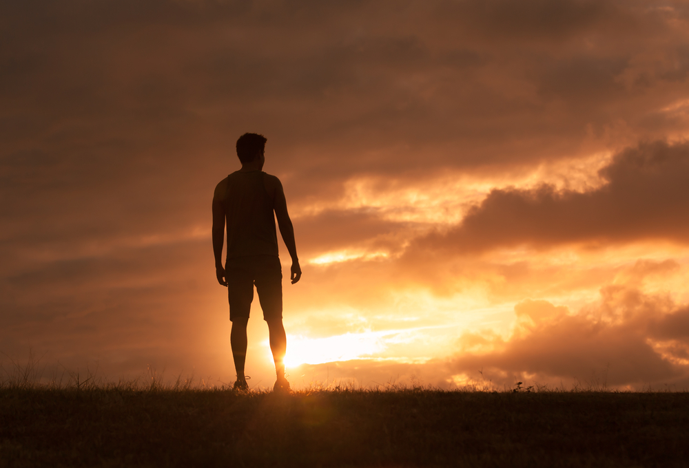Young men stares at sunset